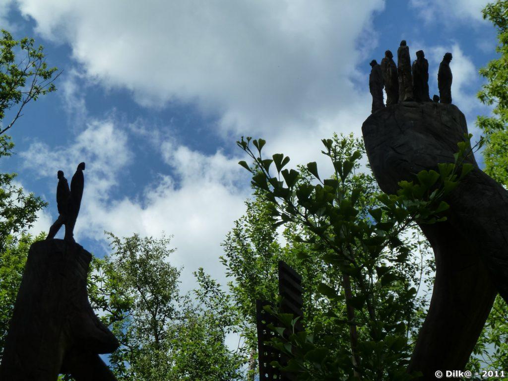 Silhouettes humaines en haut de la sculpture de bois nommée « Humanité »
