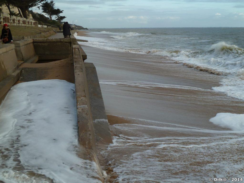 Les vagues montent jusqu'au mur de la promenade côtière