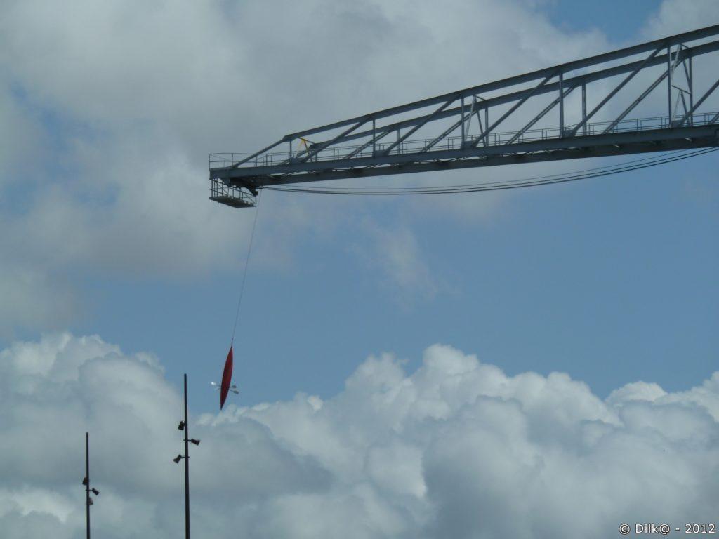 Un canoë qui pend au dessus du vide au bout d'un câble de grue