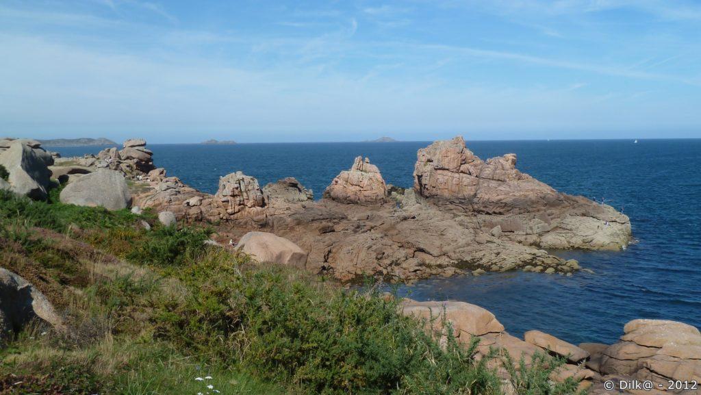 Derrière les blocs de granit rose, l'île Rouzic au loin