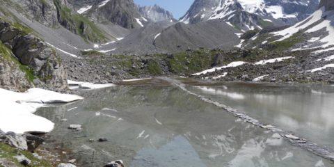 Le lac des Vaches avec les reflets de la Grande Casse et le passage à gué sur des dalles