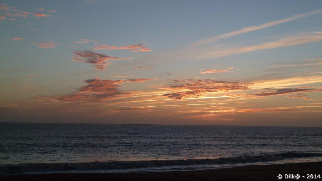 Après le coucher du soleil, les lumières orange éclairent les petits nuages