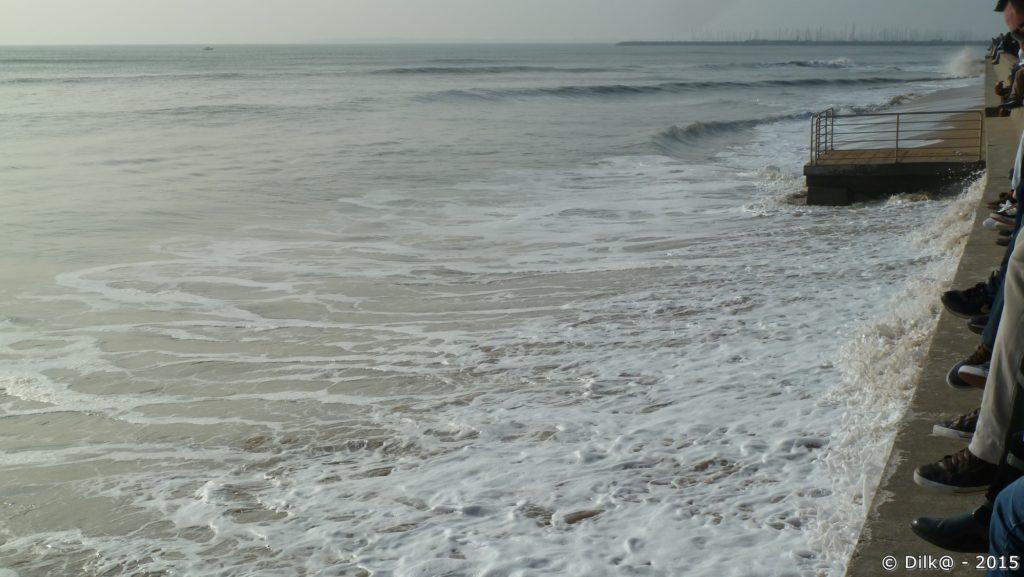 Les touristes alignés sur le mur qui regardent le spectacle des vagues